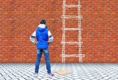 Το μικρό κορίτσι επέσυρε την προσοχή με την κιμωλία σε έναν τουβλότοιχο τη σκάλα για να υπερνικήσει αυτόν τον τοίχο Στοκ Φωτογραφία