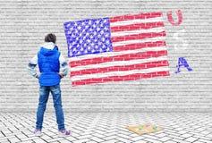 Το μικρό κορίτσι επέσυρε την προσοχή σε έναν γκρίζο τουβλότοιχο την ΑΜΕΡΙΚΑΝΙΚΗ σημαία Στοκ Φωτογραφία