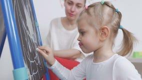 Το μικρό κορίτσι επισύρει την προσοχή με την κιμωλία στον πίνακα στο βρεφικό σταθμό Το Mom κάθεται εκτός από την και θαυμάζει το  απόθεμα βίντεο