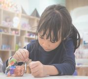 Το μικρό κορίτσι επισύρει την προσοχή σε μια κούκλα ασβεστοκονιάματος στην τάξη Στοκ Φωτογραφία