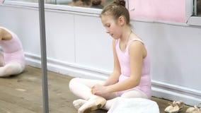 Το μικρό κορίτσι εφήβων σε ένα ρόδινο leotard, προετοιμάζεται για το κλασσικό μάθημα χορού μπαλέτου σε ένα σχολείο μπαλέτου αυτή  απόθεμα βίντεο