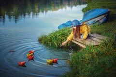 Το μικρό κορίτσι θέτει σε λειτουργία τα χρωματισμένα σκάφη εγγράφου στην ακτή της λίμνης Στοκ Εικόνες