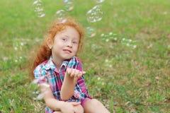 Το μικρό κορίτσι θέτει στη χλόη μεταξύ των φυσαλίδων το καλοκαίρι Στοκ φωτογραφίες με δικαίωμα ελεύθερης χρήσης