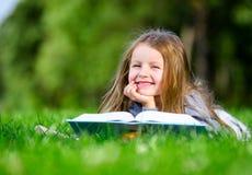 Το μικρό κορίτσι διαβάζει το βιβλίο στη χλόη στοκ φωτογραφία με δικαίωμα ελεύθερης χρήσης
