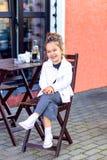 Το μικρό κορίτσι κάθεται σε έναν καφέ στην οδό και το χαμόγελο στοκ εικόνες με δικαίωμα ελεύθερης χρήσης