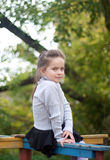 Το μικρό κορίτσι κάθεται σε ένα παλαιό ιπποδρόμιο Στοκ φωτογραφία με δικαίωμα ελεύθερης χρήσης