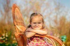 Το μικρό κορίτσι κάθεται σε μια καρέκλα Στοκ εικόνες με δικαίωμα ελεύθερης χρήσης