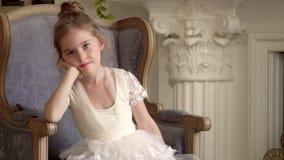 Το μικρό κορίτσι κάθεται σε μια μεγάλη καρέκλα Λίγος τομέας ballerina των επαγγελμάτων φιλμ μικρού μήκους