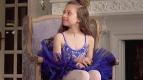 Το μικρό κορίτσι κάθεται σε μια μεγάλη καρέκλα Το μικρό ballerina σε ένα μπλε πακέτο κοιτάζει σε μια απόσταση Το κορίτσι κάθεται  απόθεμα βίντεο