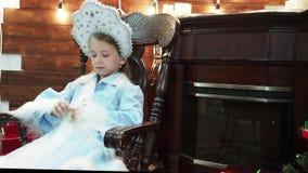 Το μικρό κορίτσι κάθεται σε μια ξύλινη καρέκλα κοντά σε μια εστία απόθεμα βίντεο