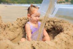 Το μικρό κορίτσι κάθεται στην τρύπα άμμου πίσω από τη ροή του νερού στην παραλία Στοκ Φωτογραφία