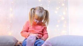 Το μικρό κορίτσι κάθεται στο πάτωμα στο δωμάτιο με το ντεκόρ Χριστουγέννων και παίζει το παιχνίδι στο τηλέφωνο απόθεμα βίντεο