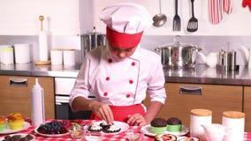 Το μικρό κορίτσι κάνει ένα κέικ με την κρέμα απόθεμα βίντεο