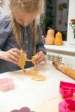 Το μικρό κορίτσι κάνει ένα μπισκότο Στοκ Εικόνες