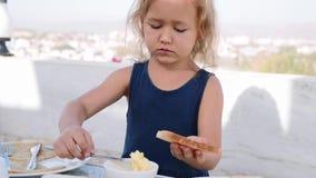 Το μικρό κορίτσι κάνει το σάντουιτς με το βούτυρο για το πρόγευμα απόθεμα βίντεο