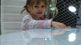 Το μικρό κορίτσι κάνει τα πρόσωπα μπροστά από έναν καθρέφτη φιλμ μικρού μήκους