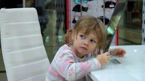 Το μικρό κορίτσι κάνει τα πρόσωπα μπροστά από έναν καθρέφτη απόθεμα βίντεο