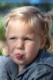 Το μικρό κορίτσι κάνει τα πρόσωπα Στοκ Εικόνες
