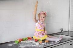 Το μικρό κορίτσι κάνει τη ζύμη στην κουζίνα με την κυλώντας καρφίτσα Στοκ φωτογραφία με δικαίωμα ελεύθερης χρήσης
