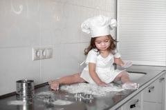 Το μικρό κορίτσι κάνει τη ζύμη στην κουζίνα με την κυλώντας καρφίτσα Στοκ Εικόνες