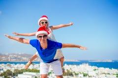 Το μικρό κορίτσι και ο ευτυχής μπαμπάς στα καπέλα Santa απολαμβάνουν τις διακοπές Χριστουγέννων με την όμορφη άποψη Στοκ εικόνα με δικαίωμα ελεύθερης χρήσης