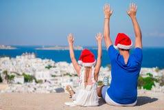 Το μικρό κορίτσι και ο ευτυχής μπαμπάς στα καπέλα Santa απολαμβάνουν τις διακοπές Χριστουγέννων με την όμορφη άποψη Στοκ φωτογραφία με δικαίωμα ελεύθερης χρήσης