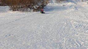 Το μικρό κορίτσι και ο πατέρας της γλιστρούν στο snowtube από το λόφο στη χειμερινή ηλιόλουστη ημέρα απόθεμα βίντεο