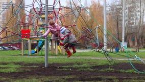 Το μικρό κορίτσι και το αγόρι στα θερμά ενδύματα αναρριχούνται στην παιδική χαρά φιλμ μικρού μήκους