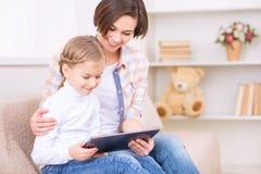 Το μικρό κορίτσι και το mom της χρησιμοποιούν την ταμπλέτα Στοκ Εικόνα