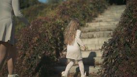 Το μικρό κορίτσι και το mom της αναρριχούνται στα σκαλοπάτια υπαίθρια κίνηση αργή απόθεμα βίντεο