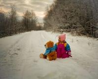 Το μικρό κορίτσι και Teddy αντέχουν το παιχνίδι υπαίθριο Στοκ Εικόνες