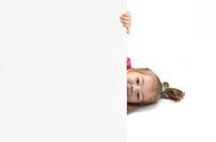 Το μικρό κορίτσι κοιτάζει έξω λόγω ενός φύλλου του εγγράφου στοκ εικόνα με δικαίωμα ελεύθερης χρήσης
