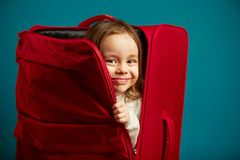 Το μικρό κορίτσι κοιτάζει από την κόκκινη βαλίτσα, πορτρέτο του εύθυμου παιδιού στο μπλε υπόβαθρο στοκ εικόνες