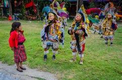 Το μικρό κορίτσι κοιτάζει επίμονα στους ντυμένους με κοστούμι εκτελεστές - χορός των ιπτάμενων Στοκ εικόνα με δικαίωμα ελεύθερης χρήσης