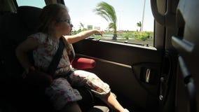 Το μικρό κορίτσι κοιτάζει μέσω του ανοικτού αυτοκινήτου παραθύρων φιλμ μικρού μήκους