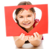 Το μικρό κορίτσι κοιτάζει μέσω του προτύπου καρδιών Στοκ εικόνα με δικαίωμα ελεύθερης χρήσης