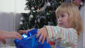 Το μικρό κορίτσι κοιτάζει σε μια συσκευασία με ένα δώρο πλησίον απόθεμα βίντεο