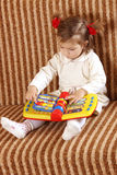 Το μικρό κορίτσι κοιτάζει στο βιβλίο Στοκ εικόνες με δικαίωμα ελεύθερης χρήσης