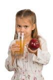 Το μικρό κορίτσι κρατά ένα γυαλί με έναν χυμό της Apple με ένα χέρι και Στοκ φωτογραφίες με δικαίωμα ελεύθερης χρήσης