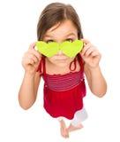 Το μικρό κορίτσι κρατά τις καρδιές πέρα από τα μάτια της Στοκ εικόνες με δικαίωμα ελεύθερης χρήσης