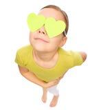 Το μικρό κορίτσι κρατά τις καρδιές πέρα από τα μάτια της στοκ εικόνες