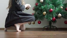 Το μικρό κορίτσι κρεμά ήπια την κόκκινη και χρυσή γιρλάντα στις πράσινες ερυθρελάτες απόθεμα βίντεο