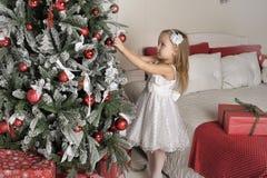 το μικρό κορίτσι κρεμά στα παιχνίδια χριστουγεννιάτικων δέντρων Στοκ Εικόνα
