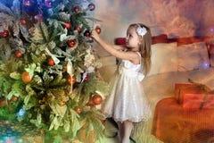 το μικρό κορίτσι κρεμά στα παιχνίδια χριστουγεννιάτικων δέντρων Στοκ φωτογραφία με δικαίωμα ελεύθερης χρήσης