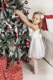 το μικρό κορίτσι κρεμά στα παιχνίδια χριστουγεννιάτικων δέντρων Στοκ φωτογραφίες με δικαίωμα ελεύθερης χρήσης