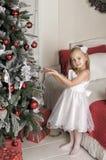 το μικρό κορίτσι κρεμά στα παιχνίδια χριστουγεννιάτικων δέντρων Στοκ εικόνες με δικαίωμα ελεύθερης χρήσης