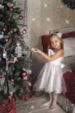 το μικρό κορίτσι κρεμά στα παιχνίδια χριστουγεννιάτικων δέντρων Στοκ Εικόνες