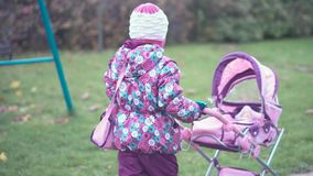 Το μικρό κορίτσι κυλά τον περιπατητή φιλμ μικρού μήκους
