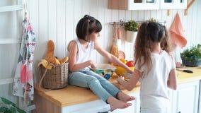 Το μικρό κορίτσι κόβει το αγγούρι στον πίνακα κουζινών, η αδελφή της κάθεται στον πίνακα, σε αργή κίνηση απόθεμα βίντεο