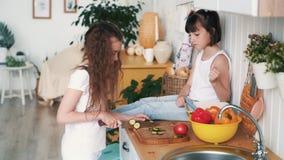 Το μικρό κορίτσι κόβει το αγγούρι στον πίνακα κουζινών, η αδελφή της κάθεται στον πίνακα, σε αργή κίνηση φιλμ μικρού μήκους